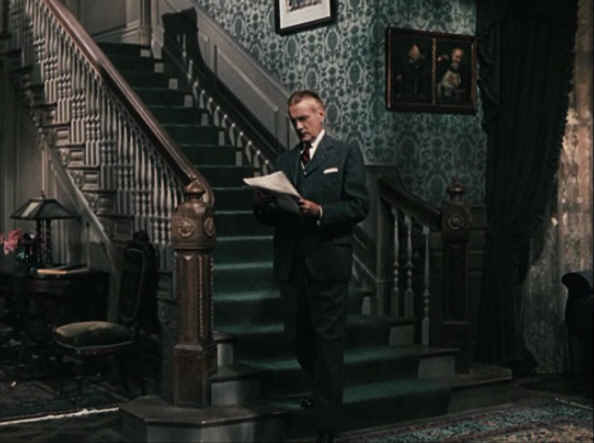Clifton Webb standing at base of staircase in Cheaper by the Dozen movie