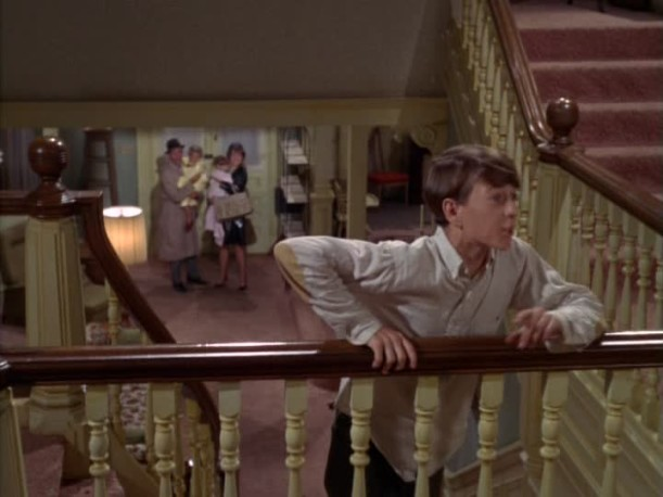 son standing on the staircase