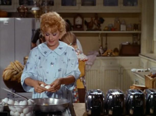 Lucille Ball preparing breakfast in kitchen