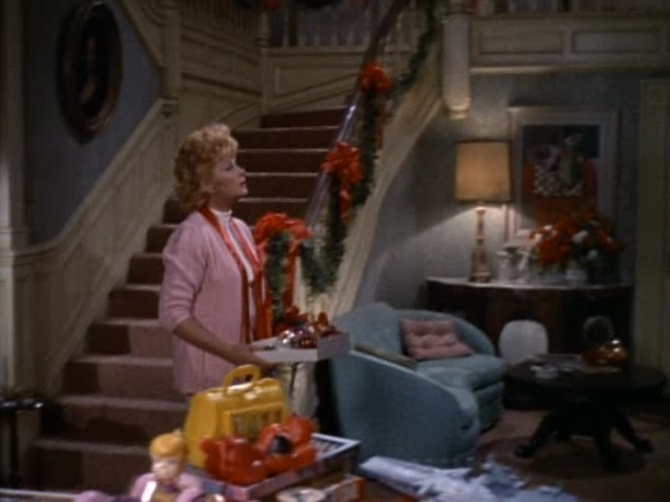 Lucille Ball standing at base of staircase