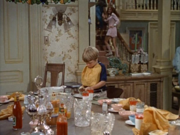 child standing at messy dining room table