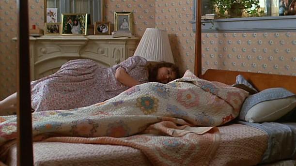 Geena Davis lying in bed with quilt