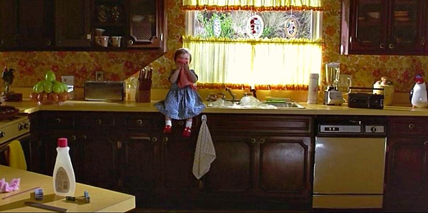 little girl sitting on counter next to sink