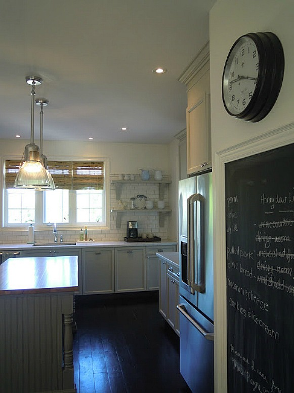 A kitchen with a clock in the middle of a room