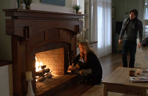 A person standing next to a fireplace, with Emily Thorne