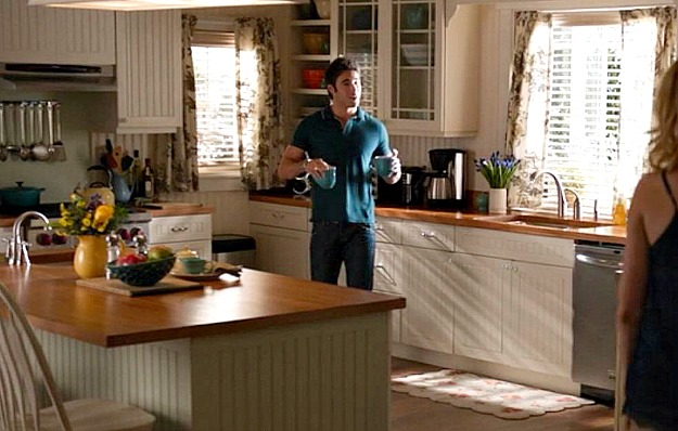 A person standing in a kitchen preparing food, with Emily Thorne