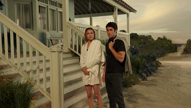 Emily and Daniel standing at the base of the steps of her beach house