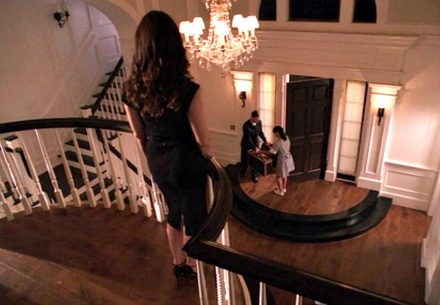 Victoria Grayson standing at top of stairs overlooking entry hall