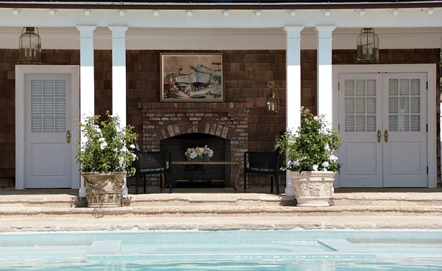 A fireplace in the covered porch of the pool house