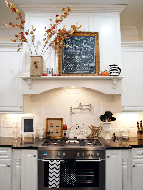 A kitchen range with shelf decorated for fall