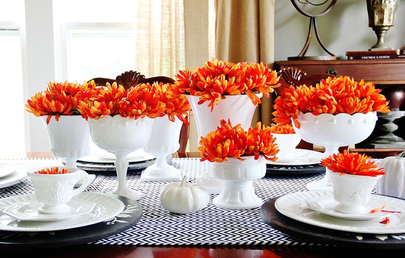 A table topped with plates, vases and orange flowers for fall