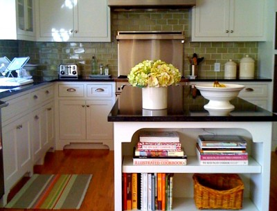 kitchen with green subway tile, white cabinets and black countertops