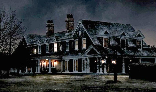 front exterior of Grayson Manor in the snow at night with lights on
