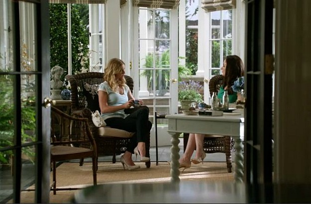 Emily and Victoria sitting in wicker chairs in the conservatory