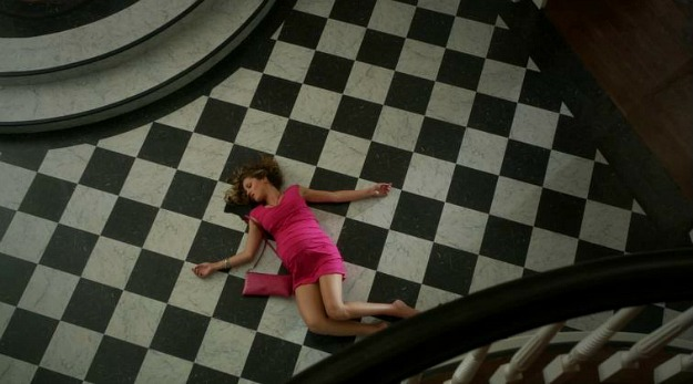 A person lying on a black and white checkerboard tiled floor