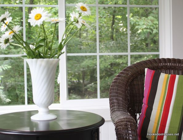 closeup of a vase of daisies beside a chair in front of a window