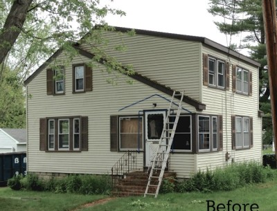 A house with tan siding and brown shutters before makeover