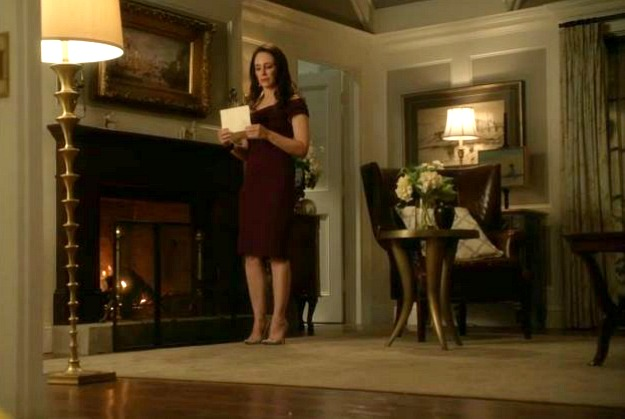 Victoria standing beside fireplace