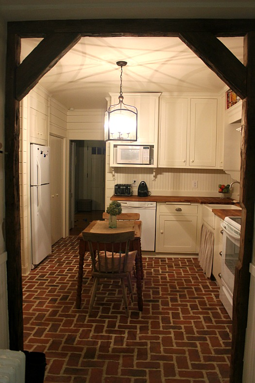 A kitchen with a red brick floor