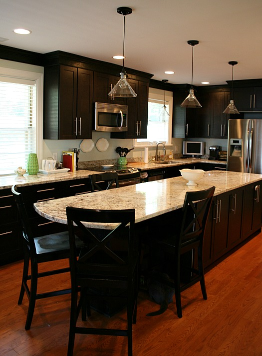 A kitchen with large marble island and black cabinets