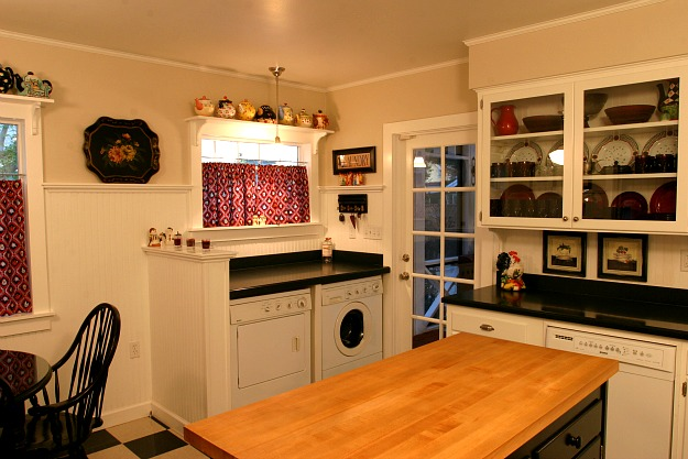 A kitchen with washer and dryer in corner of room after remodel