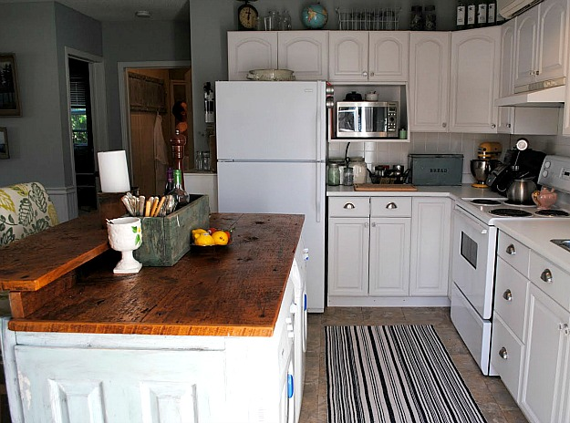 Chania\'s cottage kitchen with white cabinets and wood countertops