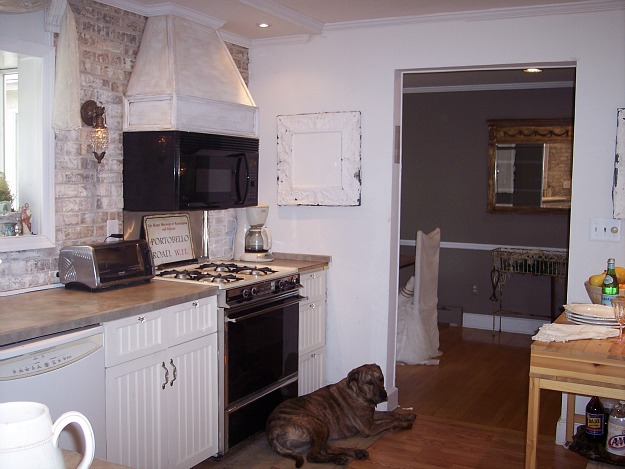 A kitchen with vent hood over microwave