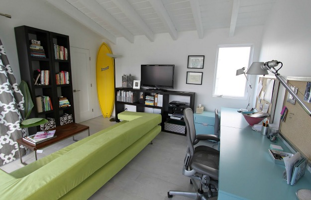 A living room with yellow surfboard in corner