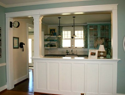 A kitchen with a large pass through to dining room