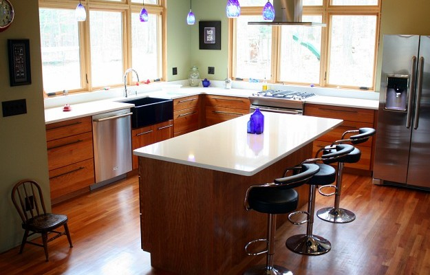A kitchen with an island in the middle of a hard wood floor