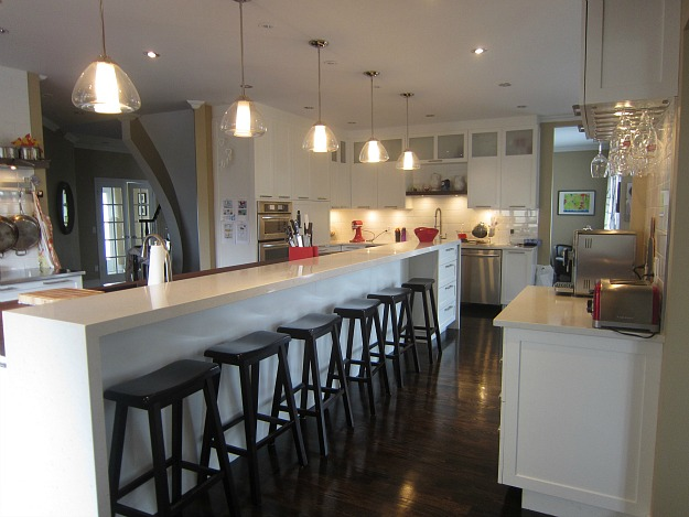 A kitchen with an extra long island and barstools