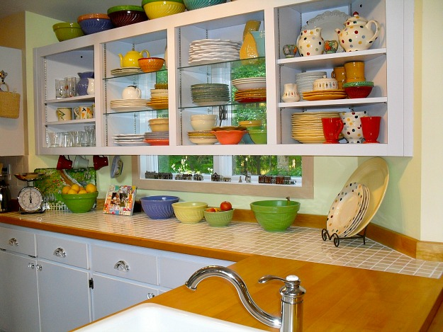 A kitchen with open cabinets filled with colorful ceramic pieces