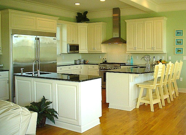 a kitchen with white cabinets and black granite countertops