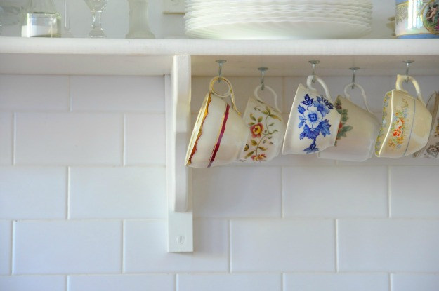 closeup of teacups hanging from hooks under kitchen shelf