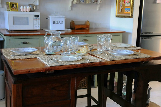 kitchen table set with glasses and plates