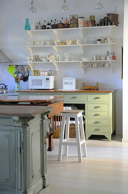 A kitchen with open shelving and pale green cabinets