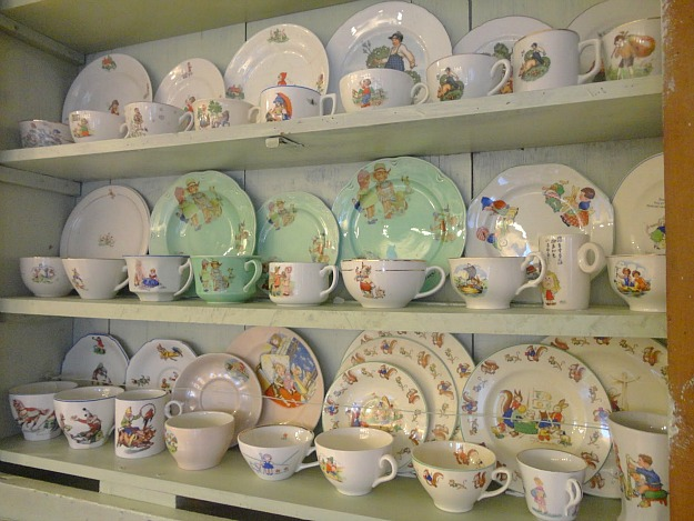 close up of china plates and teacups on display in cabinet