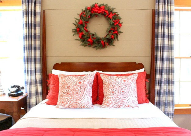 A bedroom with red and white bedding and Christmas wreath over headboard