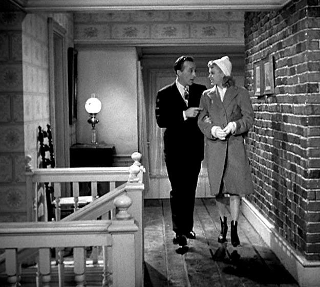 Bing Crosby and Marjorie Reynolds walking down hallway together