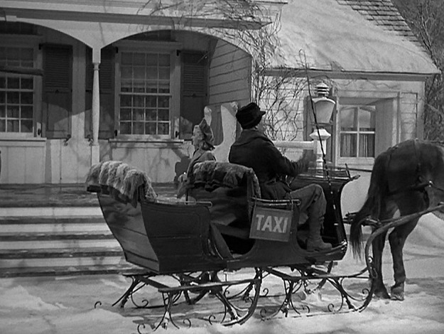 A person riding a horse drawn carriage in front of Holiday Inn in the snow