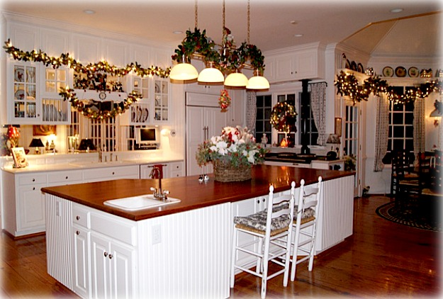 A kitchen with large white island decorated for Christmas