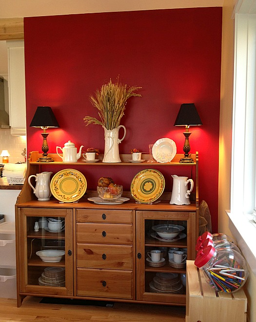 buffet set against red wall in dining area