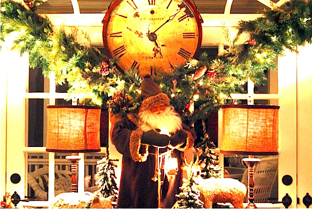 A clock in the middle of a living room with a christmas tree