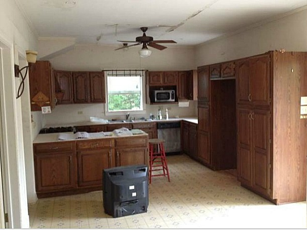 A kitchen with wooden cabinets in a room before remodel