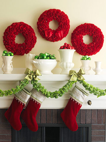 three red wreaths over mantel with stockings