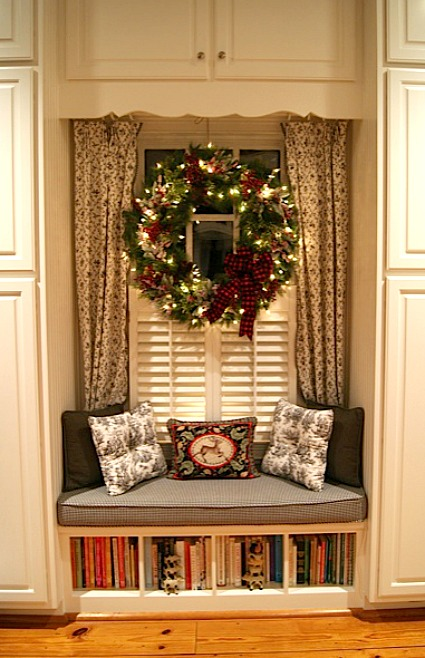 window seat with wreath hanging on window above it