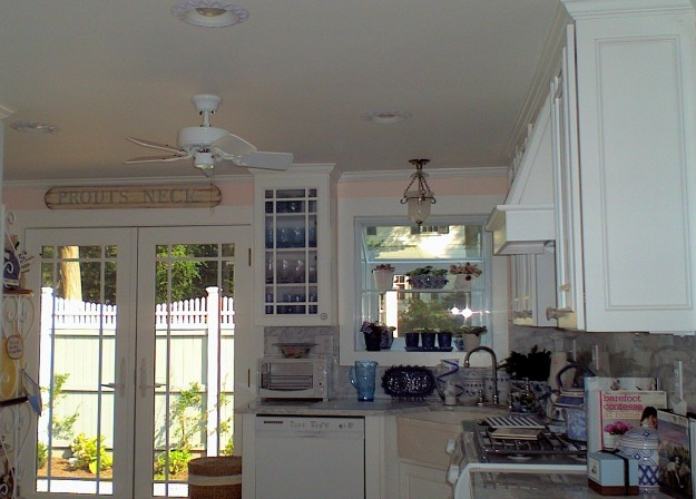 A kitchen with white cabinets and ceiling fan