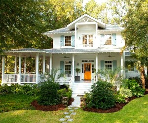 front exterior of coastal cottage that has orange door and pale blue shutters