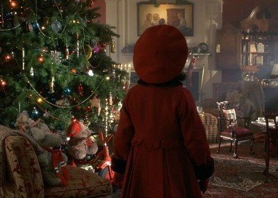 little girl in red coat and hat beside Christmas tree