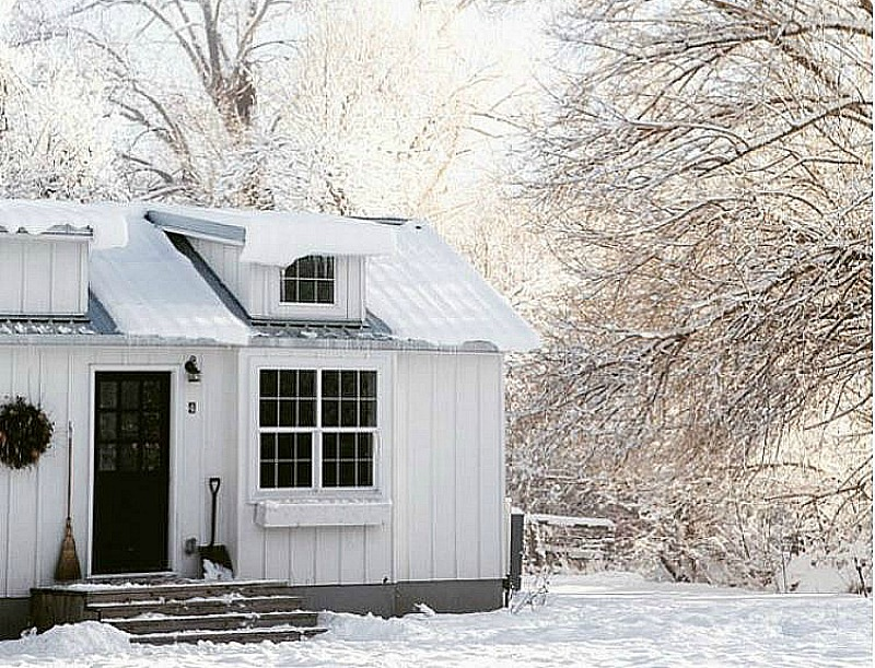 A little white house with black door covered in snow
